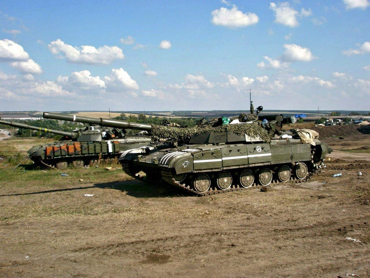 """Ukraińskie czołgi T-64BM Bułat w strefie przyfrontowej, 2014 rok. Wóz na pierwszym planie wyposażony w pancerz reaktywny """"Nóż"""" w malowaniu defiladowym. Na boku kadłuba drugiego czołgu widoczne komórki reaktywne pancerza reaktywnego Kontakt-1, zamontowane w miejsce uszkodzonych fartuchów. Na pancerzu namalowane białe pasy do szybkiej identyfikacji przynależności czołgu. (Źródło: http://wio.ru/anti/t-64bm.htm)"""
